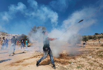 Palestinian demonstrator hurls stones at Israeli troops during a protest in the village of Ras Karkar in the occupied West Bank