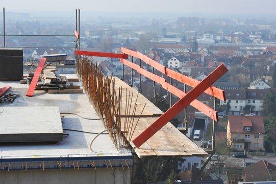 Aus der Betonwand herausstehende Baustahlenden auf dem oberen Stockwerk eines in den Steilhang gebauten modernen Mehrfamilienwohnhaus-Rohbaus mit provisorischer Absturzsicherung