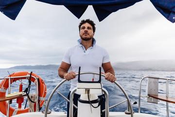 Captain of a ship sailing on a sailboat
