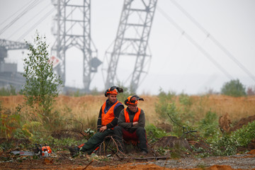"Two lumberjacks of German utility and power supplier RWE rest on a tree stump as a brown coal excavator of the Hambach open cast mining of RWE is seen behind them next to the forest ""Hambacher Wald"" near Kerpen-Buir"
