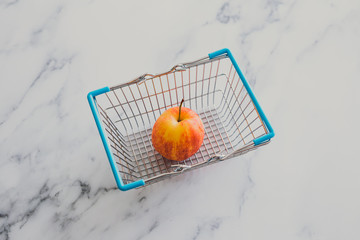 grocery store mini shopping basket with one single red apple