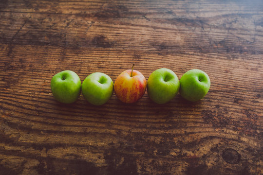 one single red apple among other green ones on wooden table