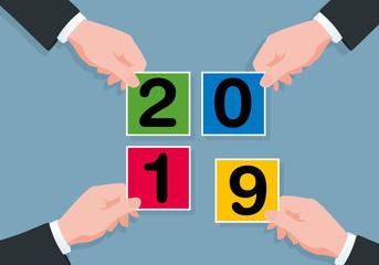 Carte de vœux sous le signe du partenariat avec 4 mains qui s'unissent pour former 2019 avec des carrés de couleurs