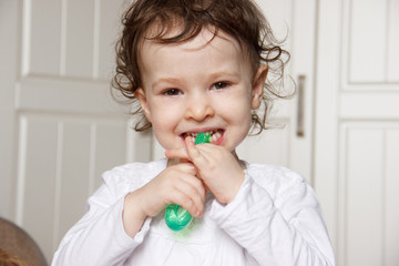 baby child brush their teeth properly with a green toothbrush