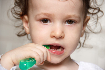 baby brush their teeth properly with a green toothbrush. Close up child portrait