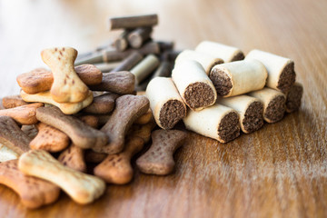 Dog tasty colored biscuits on wooden background, snacks for dogs