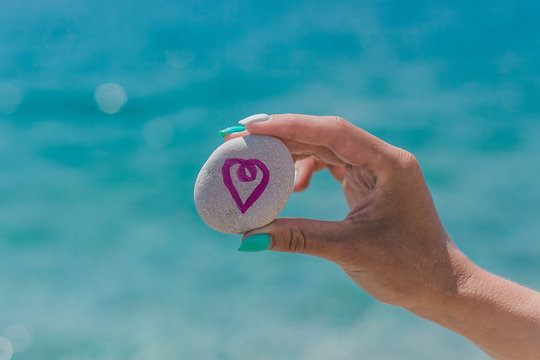 Antalya, Turkey - 31 MAY 2018: Girl holding  pebble with logo Airbnb on a beach. Travel theme. Love to travel.
