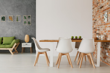 Hipster open space loft room interior with a wooden dining furniture set, green sofa and eco style...