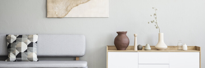 Graphic, pattern pillows on a gray sofa and a white, wooden cabinet with vases in a monochromatic living room interior with natural decorations