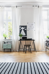 Black chair at desk in bright home office interior with windows, carpet and posters. Real photo