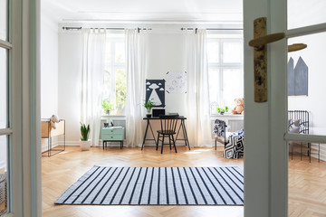 Striped carpet on wooden floor in spacious kid's room interior with chair at desk and posters. Real photo