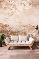 Grey wooden sofa between plant and black lamp in minimal loft interior with red brick wall. Real photo