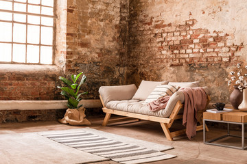 Grey wooden settee between plant and table in living room interior with rug and window. Real photo