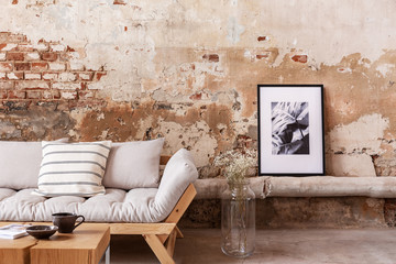 Poster and flowers next to grey wooden couch with pillows in flat interior with brick wall. Real...