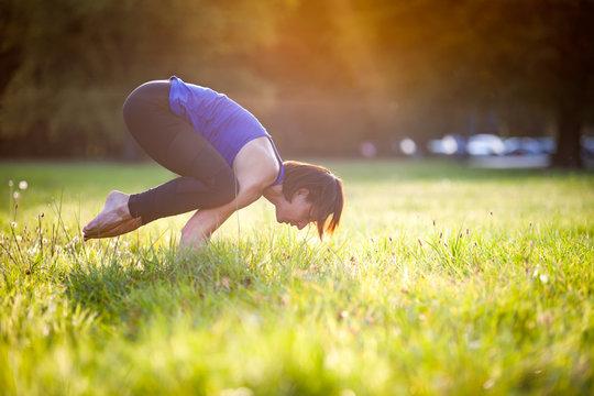 Yoga in the park, middle age woman doing bakasana exercise crane pose