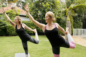 Young tattooed Caucasian woman balancing on one leg while practising yoga with professional female yoga teacher outdoors
