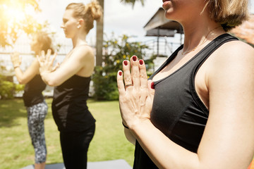 Close-up view of unrecognizable woman holding hands in namaste while having morning yoga practice outdoors