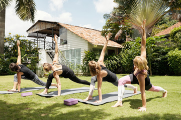 Young Caucasian women practising revolved side angle yoga pose with qualified female teacher outdoors