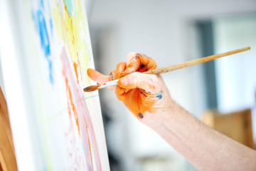 Male artist hand, holding brush and painting rich orange paint.