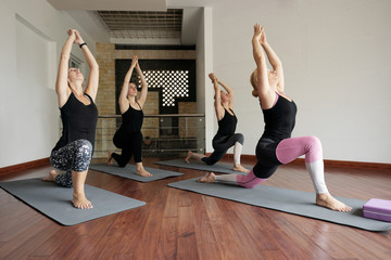 Group of young Caucasian women practising asanas with professional female yoga teacher in yoga studio