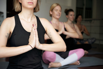 Close-up view of young Caucasian women meditating in yoga studio, sitting in lotus pose and holding hands in namaste