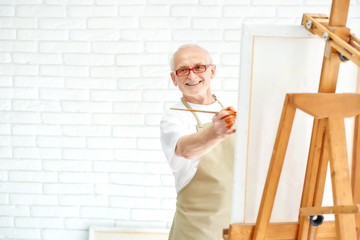 Handsome senior painter drawing colorful painting at bright studio.
