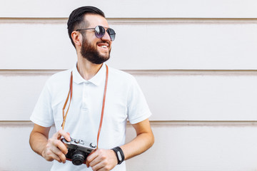 Stylish hipster with a beard and a camera standing near a white wooden wall