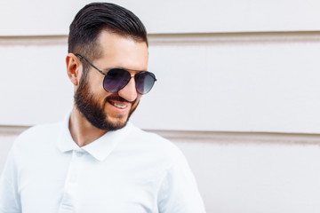 Stylish hipster in a white t-shirt and with a beard, standing near a white wooden wall