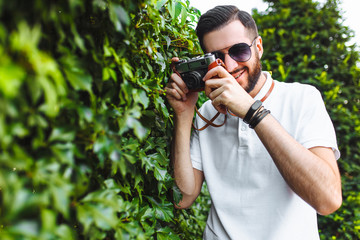 Stylish hipster with a beard and a camera, taking pictures, walking around the city