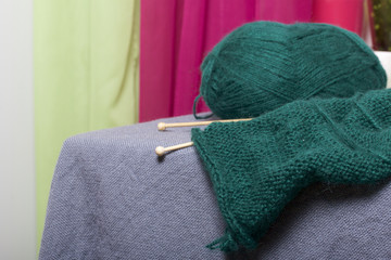 Knitting with wooden knitting. A ball of dark green thread and wooden knitting needles in an unfinished knit.