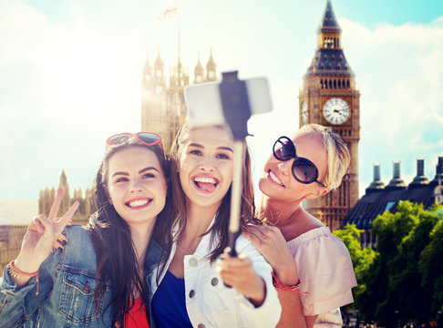summer vacation, holidays, travel, technology and people concept- group of smiling young women taking picture with smartphone on selfie stick over london city and big ben tower background