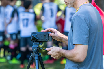 Man recording football match with his video camera on a tripod at an outdoor field