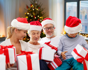 christmas, holidays and people concept - happy family in santa hats with gifts sitting on couch at home