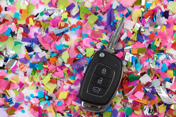 Car key on confetti background