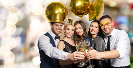 celebration, luxury and holidays concept - happy friends with golden party props clinking champagne glasses over festive lights background