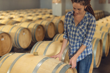 Woman winemaker checks oak wine barrels in which red wine is aged in the basement of the winery. Production of wine