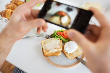 food , eating and technology concept - hands with smartphones photographing breakfast on plate
