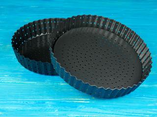Empty tart or pie trays, set on a blue wooden board