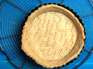 Baked pie or quiche crust in its tray, set on a cooling rack, on a blue wooden board