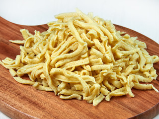 A heap of fresh Swabian dried egg noodles (spaetzle) on a wooden board