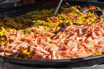Street food in France, fresh prepared paella with rice and sea food in big pan on street market, ready to eat