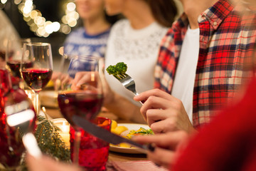 holidays, food and celebration concept - close up of friends having christmas dinner and eating