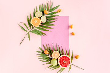 Creative layout  made of paper and summer tropical fruits on pink background. Food concept. flat lay, top view