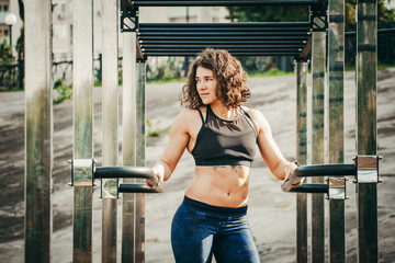 The theme women sports and health. Beautiful sexy caucasian woman with curly long hair posing on outdoor sports ground holding horizontal bar with tattoo on stomach in sports top and tight pants