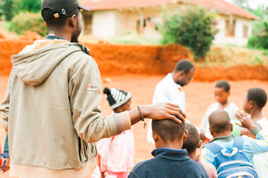 Bafoussam, Cameroon - 06 august 2018: young african teacher caress school boy while playing outside village school