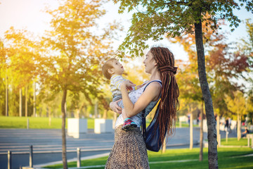 Modern happy mom with baby son walking in Sunny Park. Joy of motherhood and autumn mood