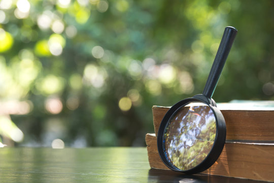 Close up of magnifying glass with old books on the wooden table and nature background.