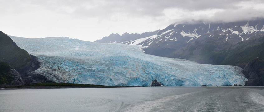 The 1.2 mile wide Aialik Glacier in Kenai Fjords National Park creeps slowly into the sea on a clouded summer day