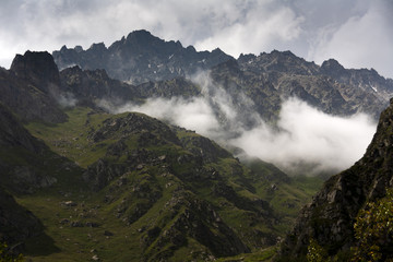 Mountain landscape, green peaks and clouds.