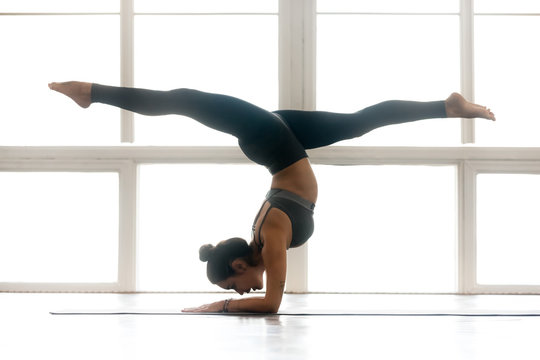Young yogi attractive woman practicing yoga, doing Pincha Mayurasana exercise, handstand pose, working out, wearing sportswear, grey pants, top, indoor full length, at yoga studio, side view
